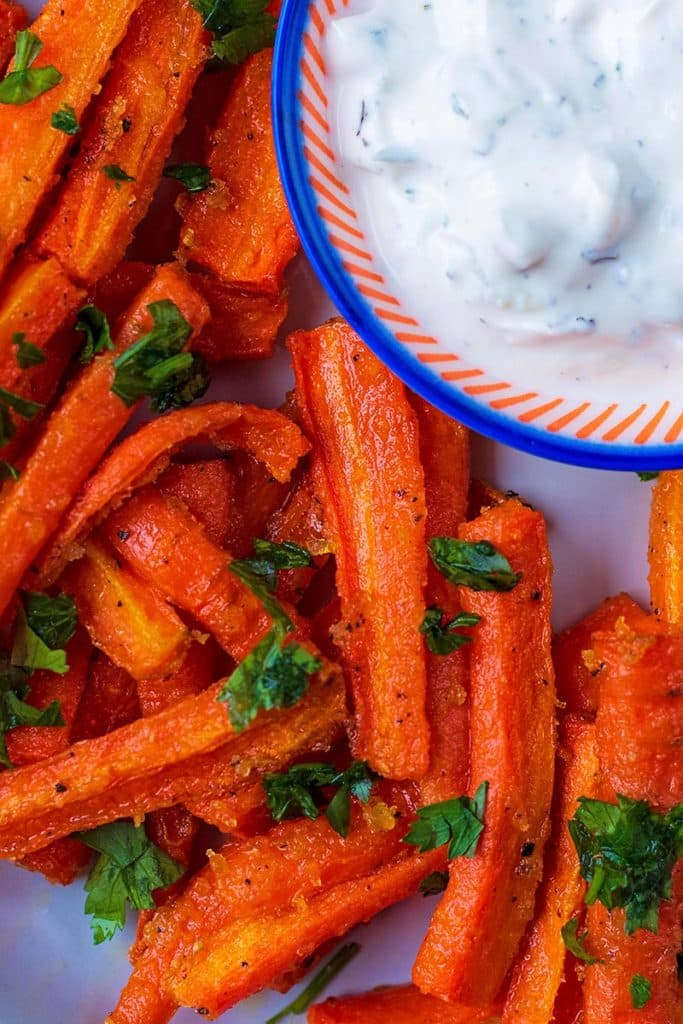 Baked carrot fries on a plate topped with chopped herbs