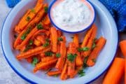 A plate of carrot fries with a small dish of dip