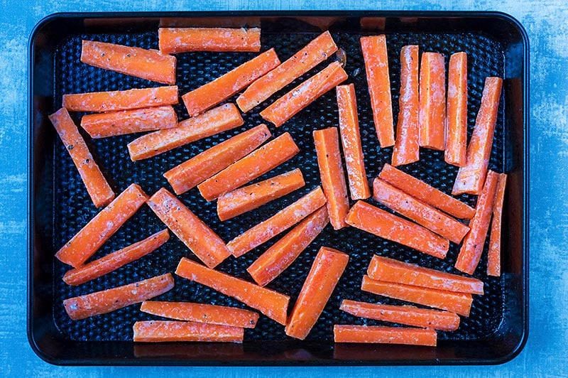 Carrot batons laid out on a black baking tray