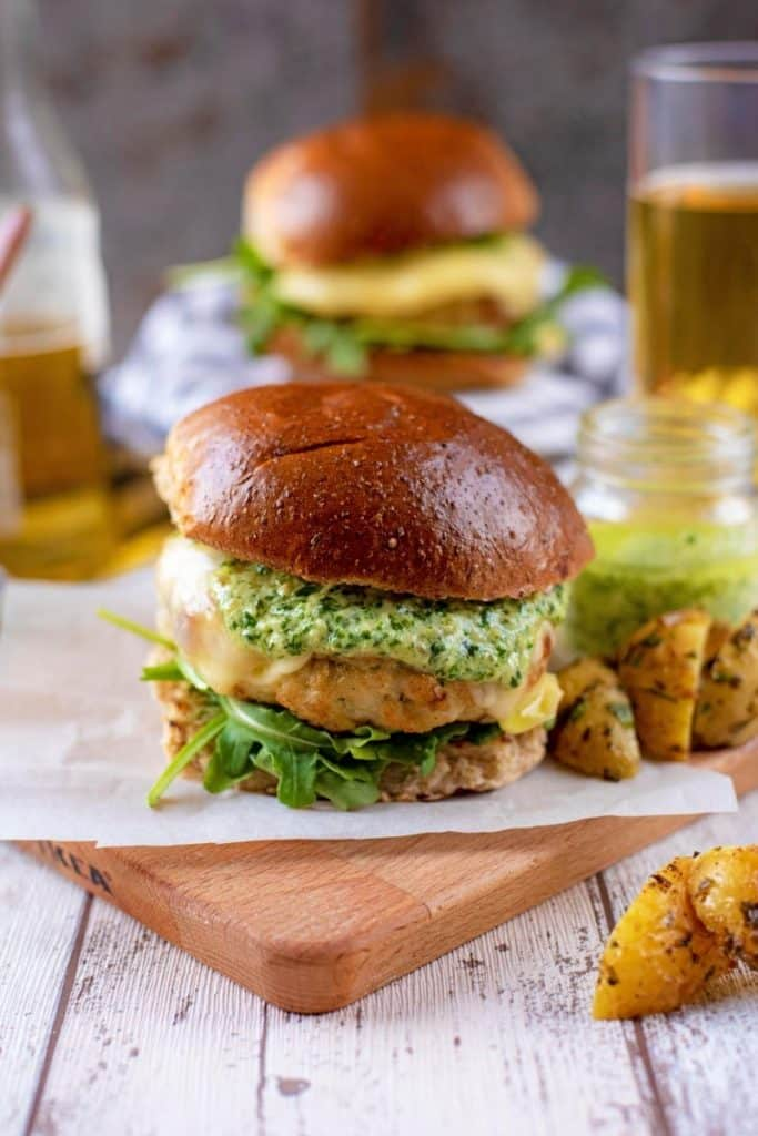 A chicken burger in a bun on a wooden board, beer and another burger in the background