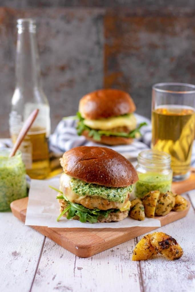Two chicken burgers with a bottle of beer and jars of pesto