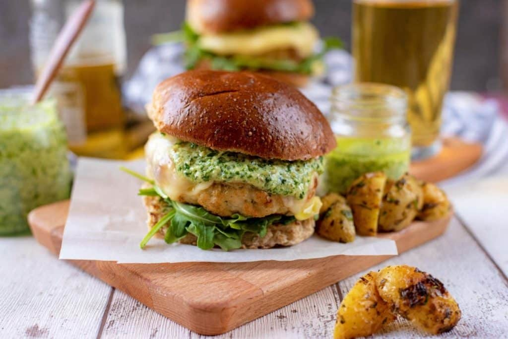 Chicken burger, potato wedges, beer and a jar of pesto on a wooden surface
