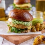 Chicken Pesto Burgers sat on a wooden serving board with potato wedges
