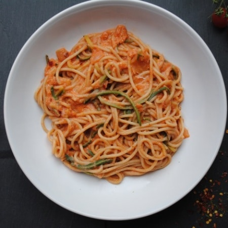 Spicy pasta in a white bowl, surrounded by vine tomatoes
