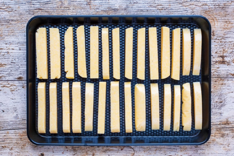 polenta cut into fries on a black baking tray
