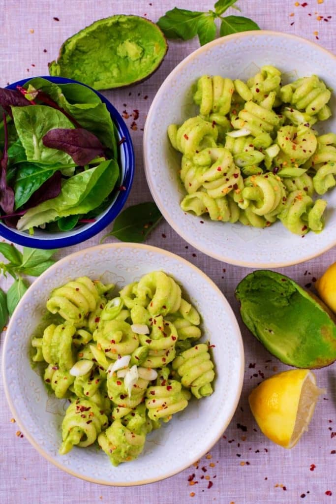Two bowls of pasta in an avocado sauce