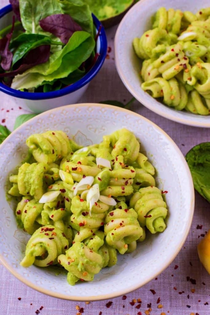 Avocado pasta in two bowls next to a side salad