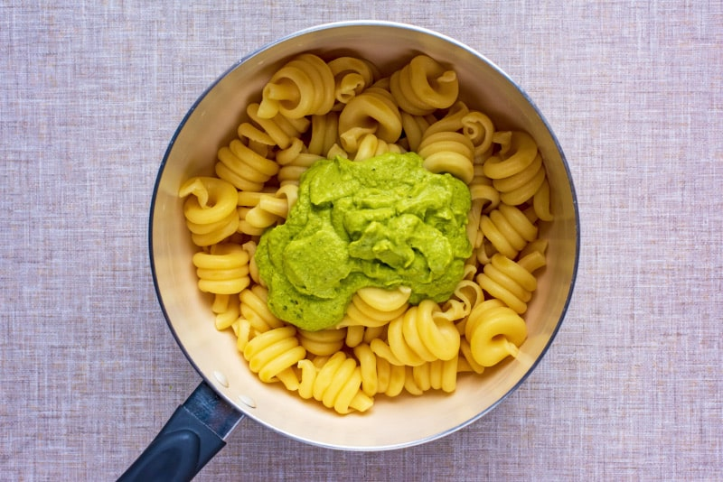 A saucepan of cooked pasta spirals with a large dollop of green sauce