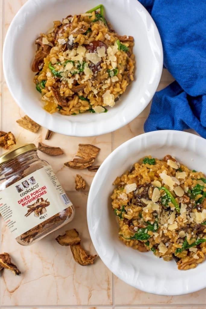 Two bowls of risotto next to a jar of Cooks&Co dried mushrooms