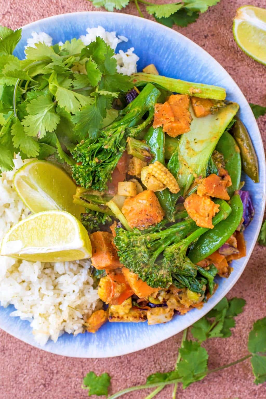 A plate of Thai Green Curry, rice and lime wedges