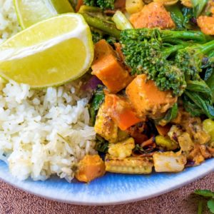 Vegetable Thai Green Curry on a blue plate with rice and a lime wedge