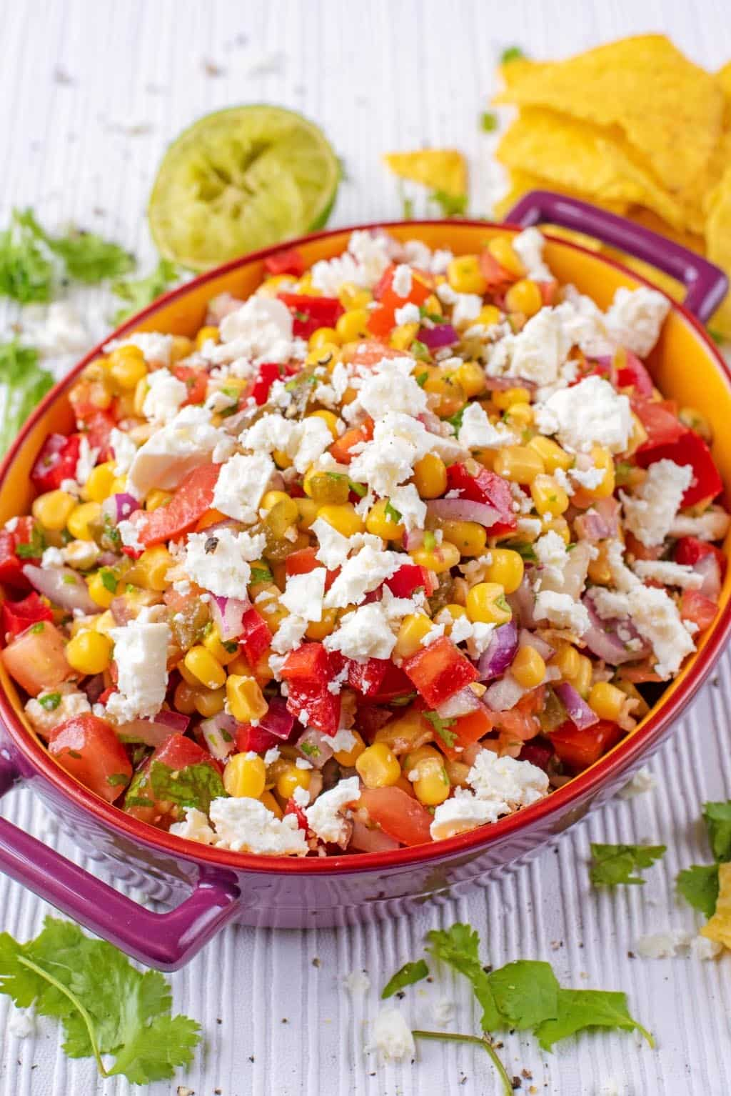 An oval dish containing a salsa of mixed corn, peppers, tomato and cheese