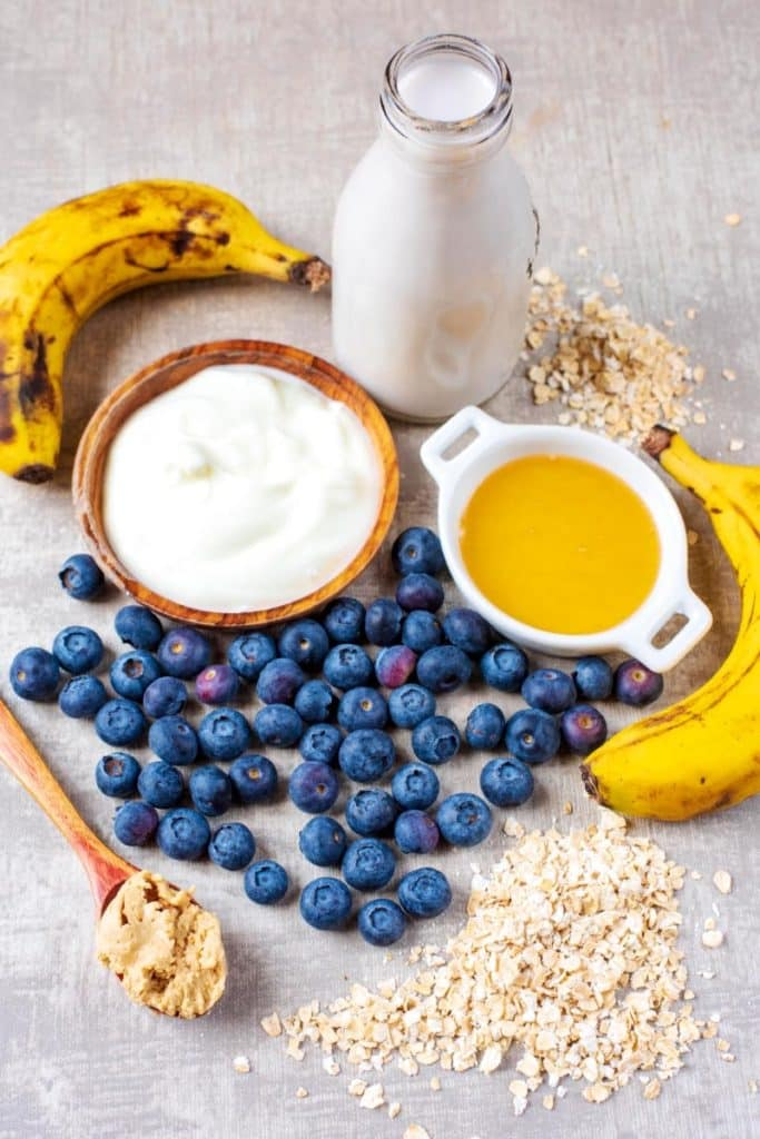 Blueberries, bananas, plain yoghurt, honey, milk and oats arranged on a wooden surface