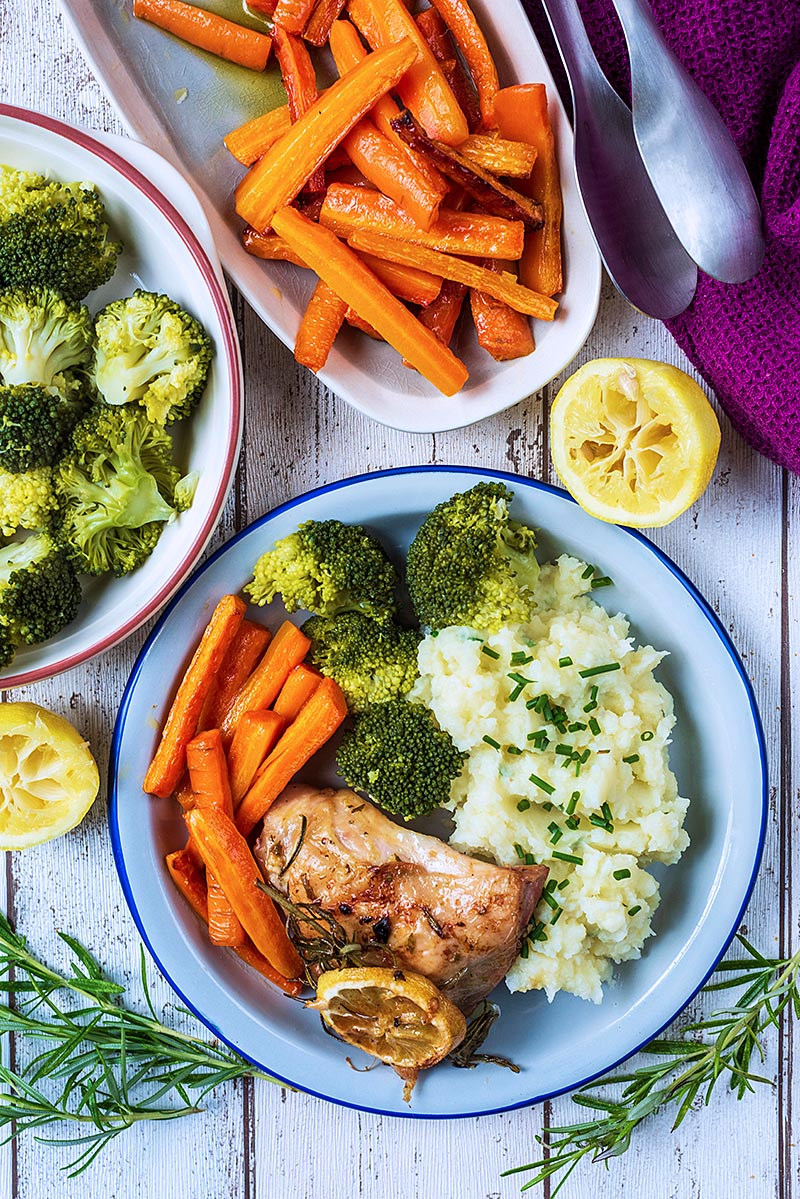 A plate with Lemon Rosemary Chicken and vegegtables next to lemon wedges, more vegetables and a purple towel
