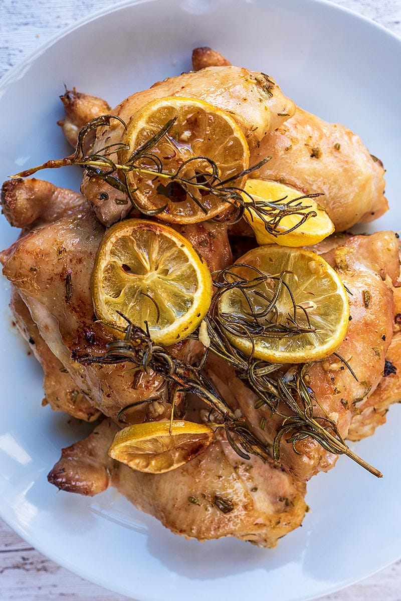 Four baked chicken thighs on a plate with lemon slices and sprigs of rosemary