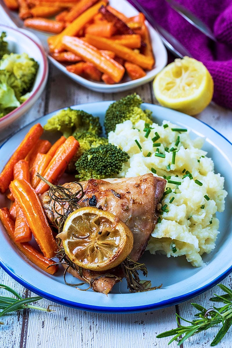 Chicken and vegetables on a white plate. A long dish of carrots is in the background