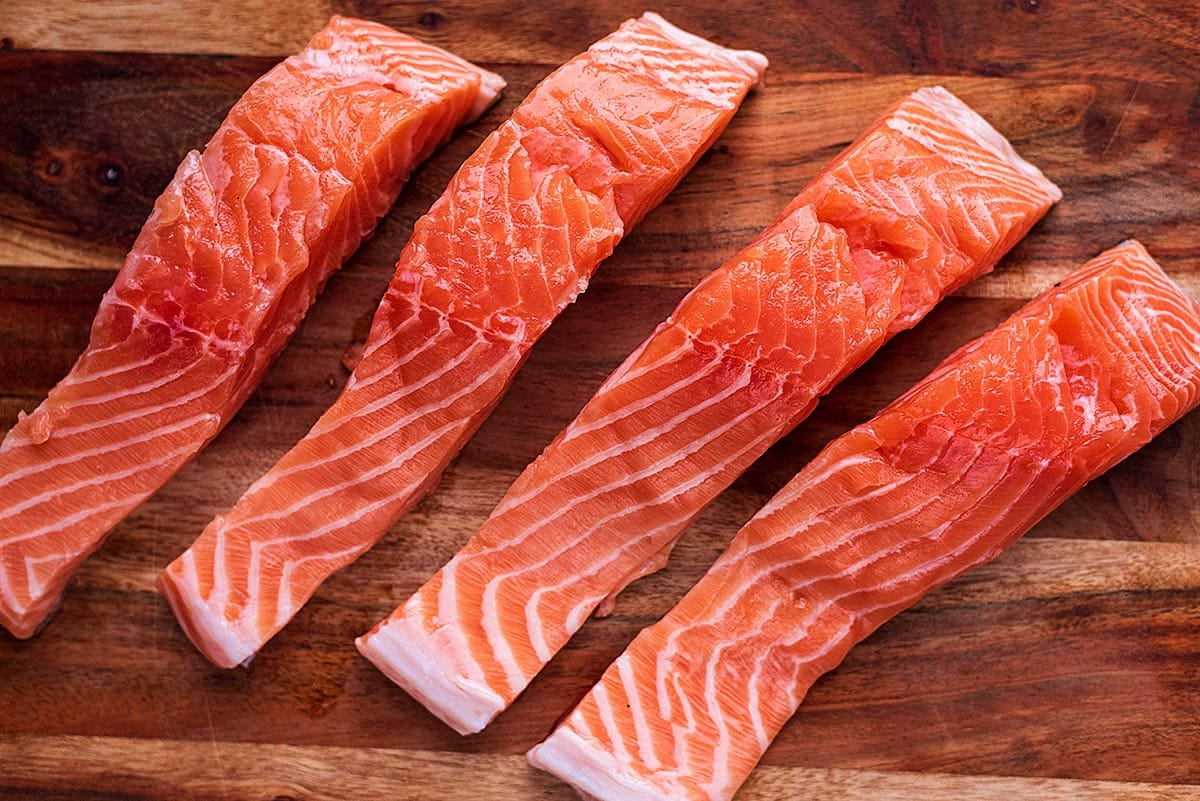 Four uncooked salmon fillets on a wooden chopping board