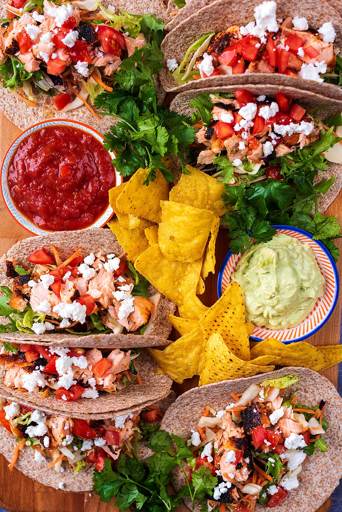 Seven salmon tacos arranged on a serving board with chips, dips and herbs