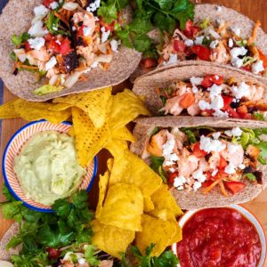 Salmon tacos arranged on a wooden board surrounded by tortilla chips and bunches of herbs
