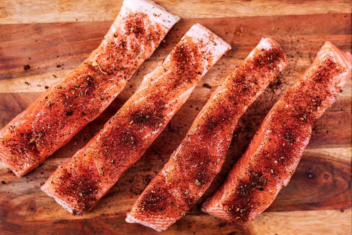 Four salmon fillets on a wooden board coated in taco seasoning