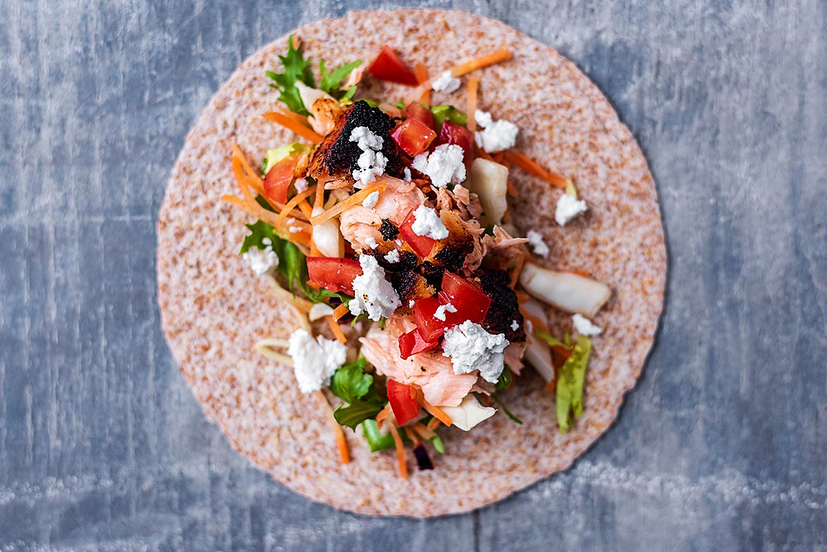 A taco made up of salad, salmon and cheese