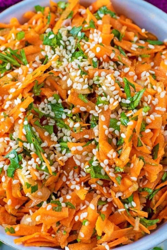 A bowl of grated carrot with herbs and sesame seeds