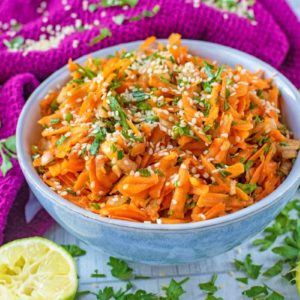 A blue bowl with grated carrot in it