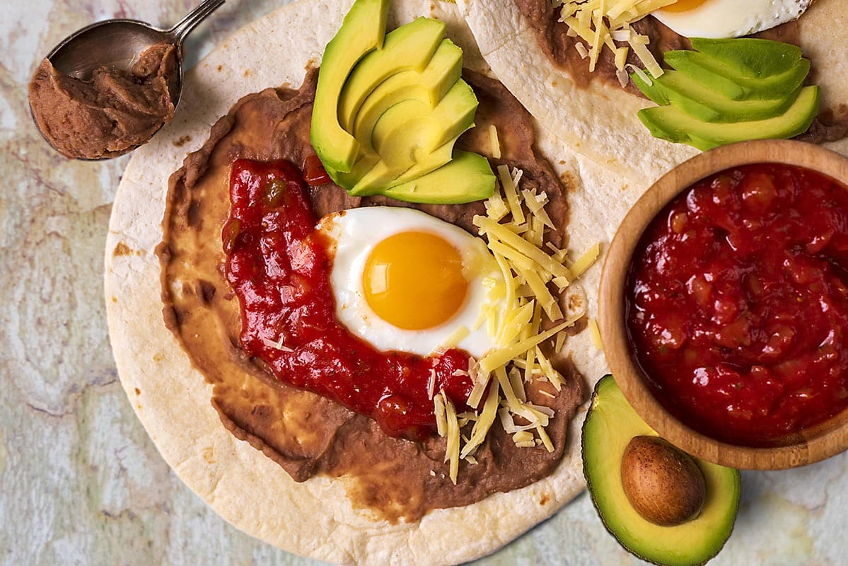 Huevos Rancheros topped with sliced avocado and grated cheese