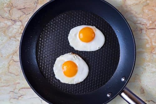 A frying pan with two fried eggs in it