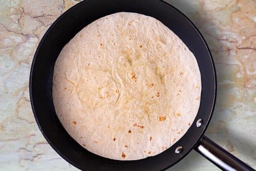 A frying pan with a flour tortilla being heated in it