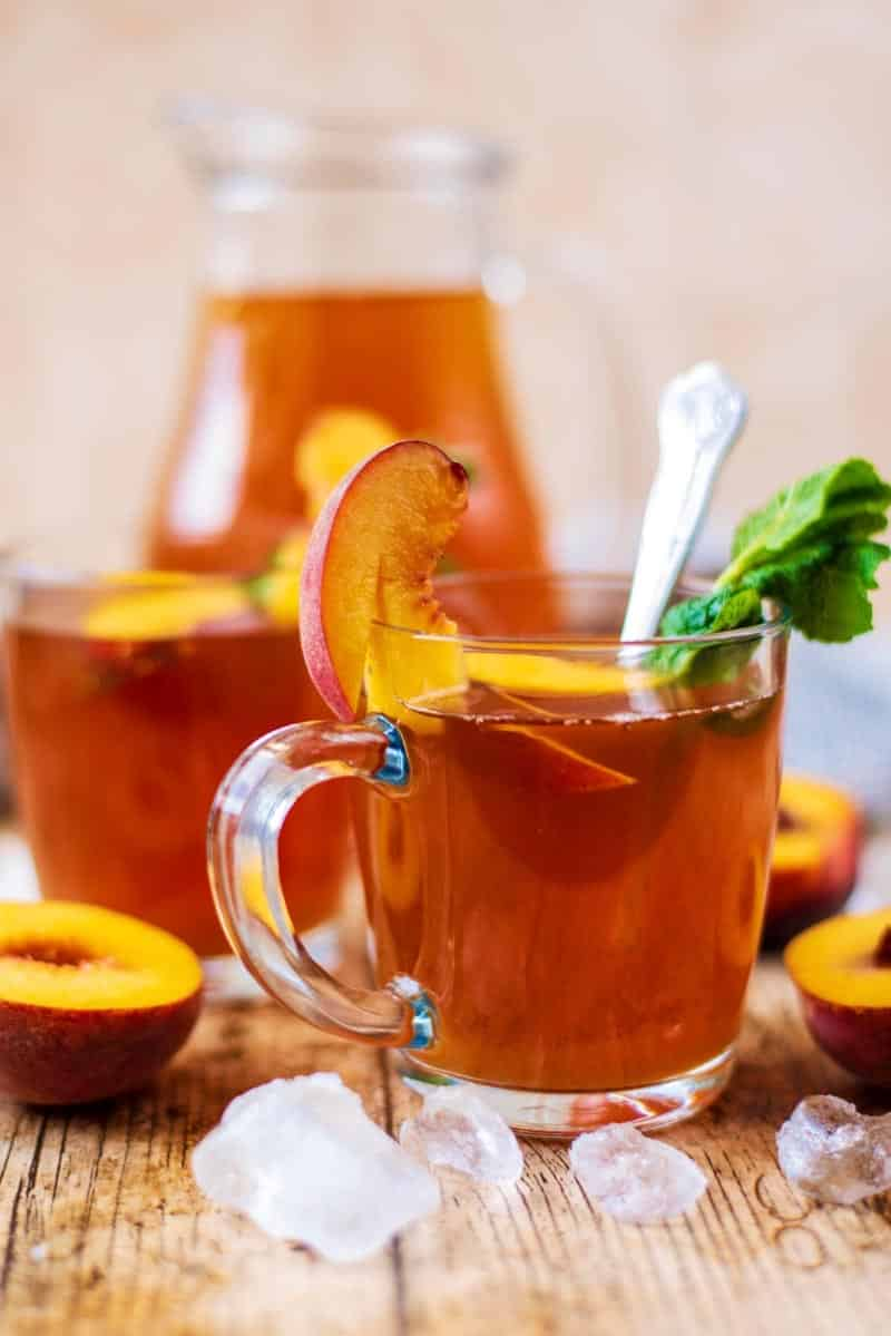 A glass of iced tea with a peach slice. mint leaves and a spoon