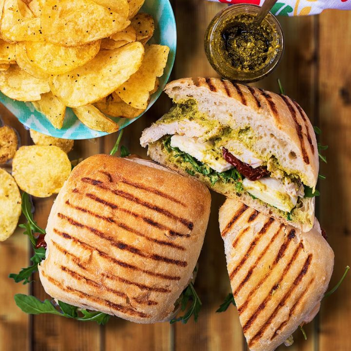 Pesto Chicken Sandwich next to a bowl of potato chips