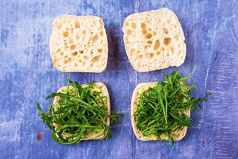 Ciabatta buns topped with pesto sauce and arugula