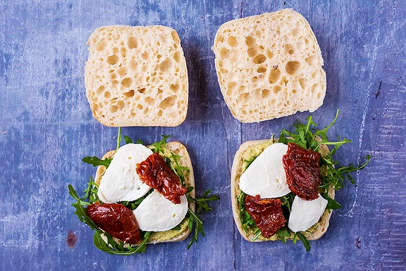 Ciabatta buns topped with arugula. mozzarella and sun dried tomatoes