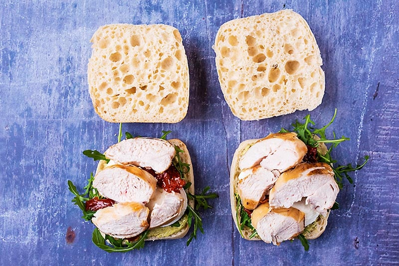 Ciabatta buns topped with arugula, cheese, tomatoes and chicken