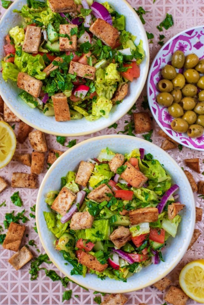 Two bowls of Fattoush Salad next to a bowl of green olives