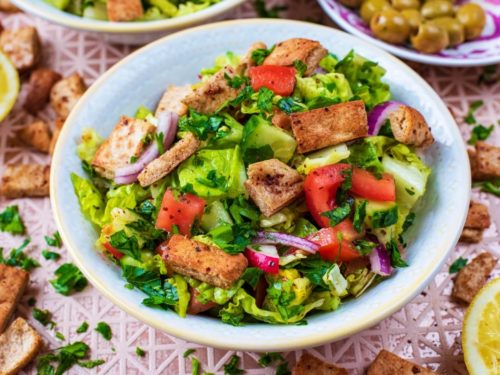 Fattoush Salad in a white bowl surrounded by various salad ingredients