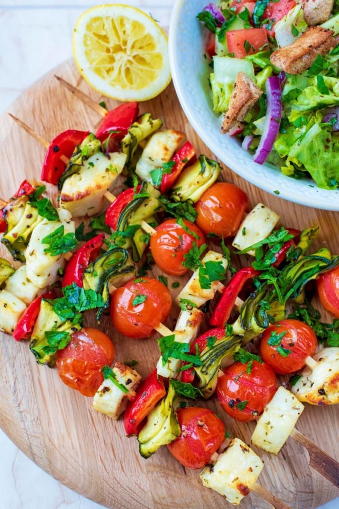 Vegetable and Halloumi Kebabs on skewers next to a bowl of salad