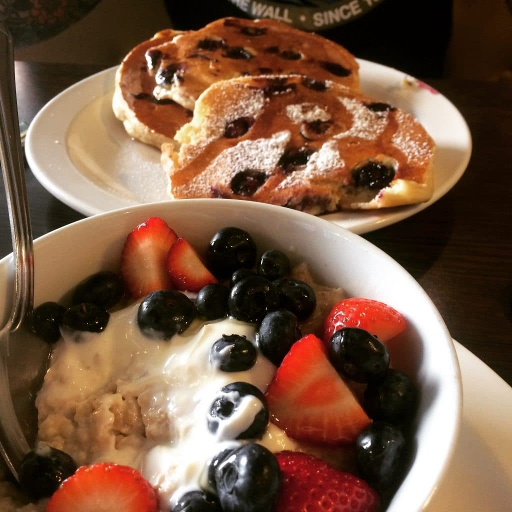 A bowl of oatmeal topped with berries in front of three large american style pancakes