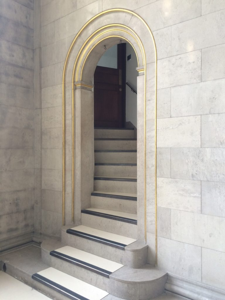 A set of stone steps leading up to an arched doorway