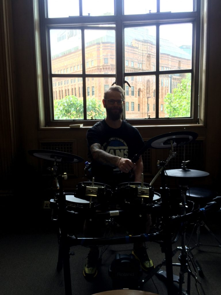 Dave sat at a set of drums in front of a large window