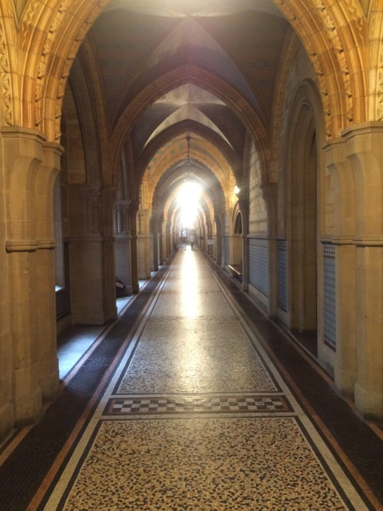 A long Gothic arch corridor with a marbled floor