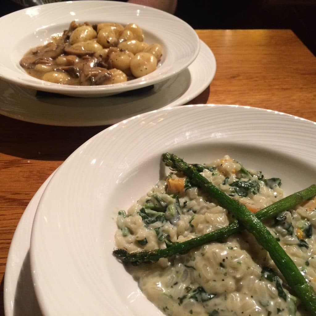 A bowl of asparagus risotto in front of a bowl of mushroom gnocchi