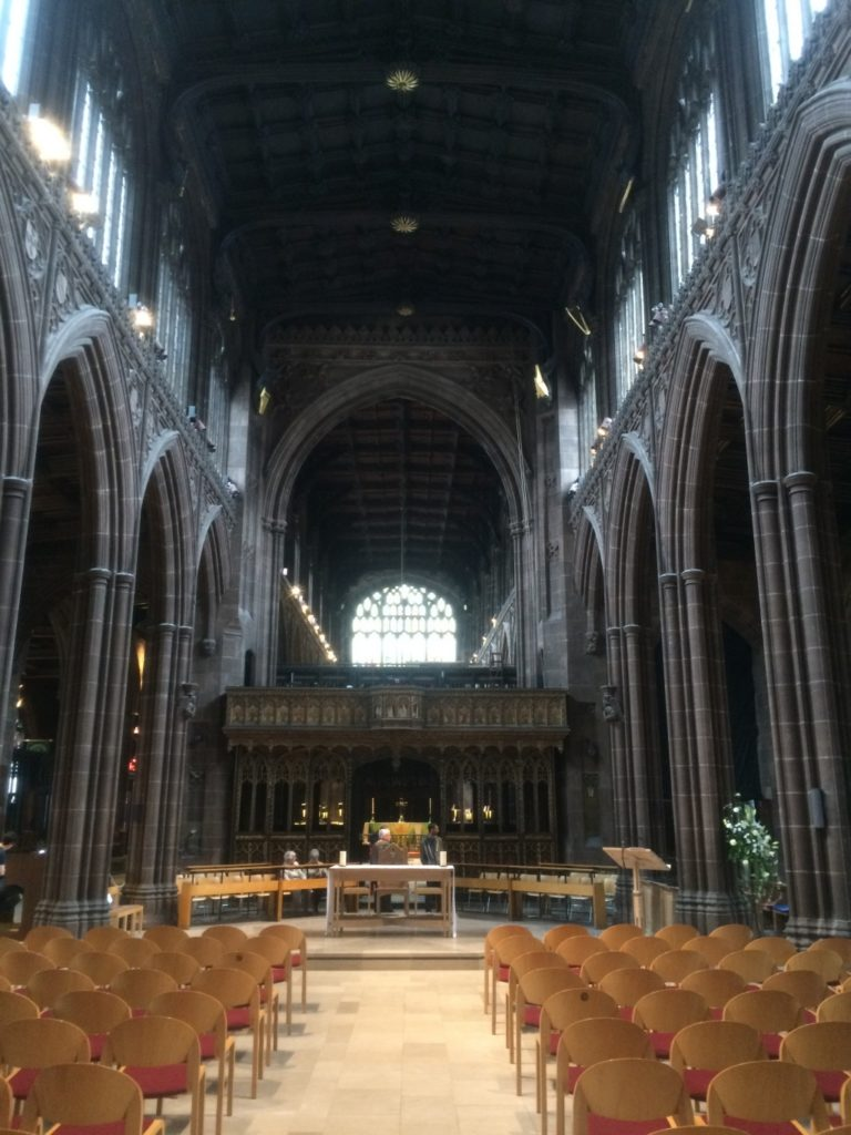 The central aisle of Manchester Cathedral showing Gothic arches either side and the pulpit at the end