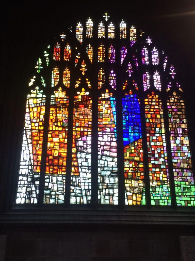 A colourful Gothic arch stained glass window