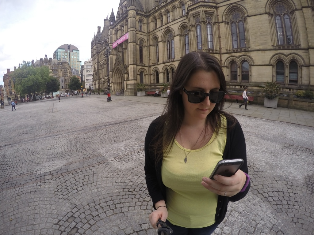 Dannii checking her phone in front of Manchester's town hall