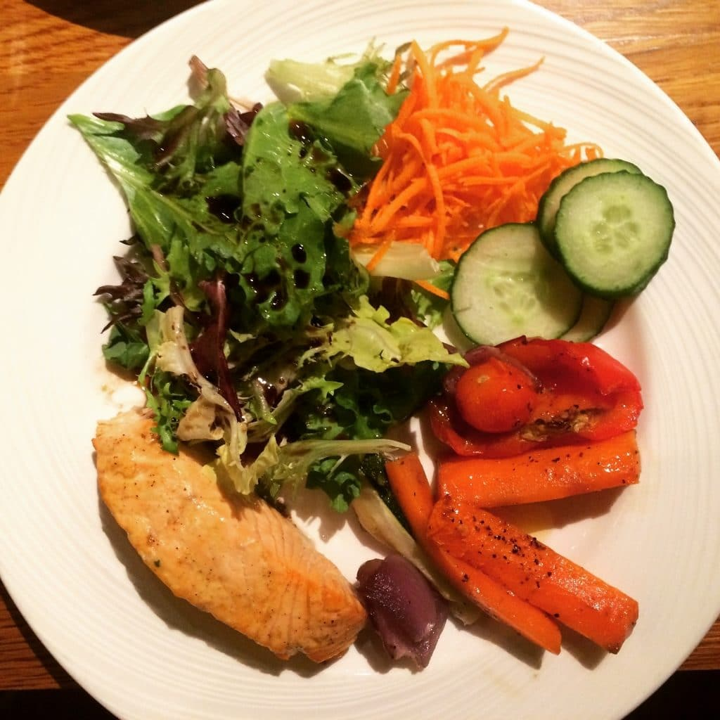 A cooked salmon filet on a plate with salad leaves, grated carrot, sliced cucumber and roasted vegetables