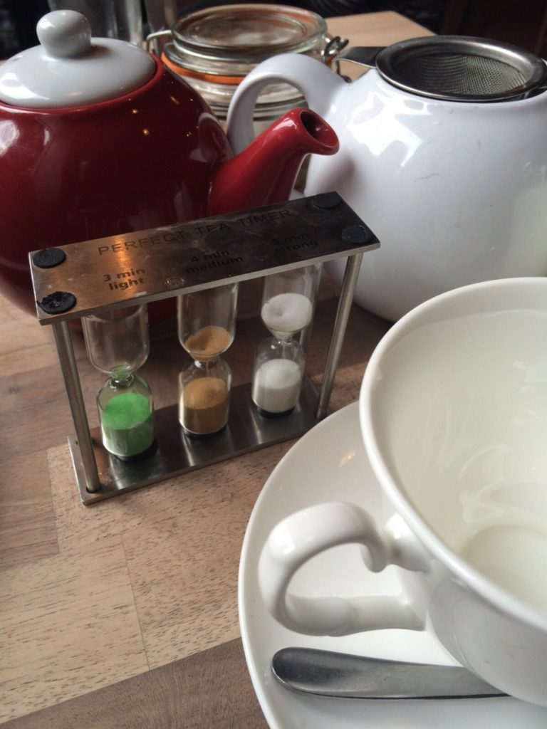 Two tea pots, a cup and saucer and a three part sand timer