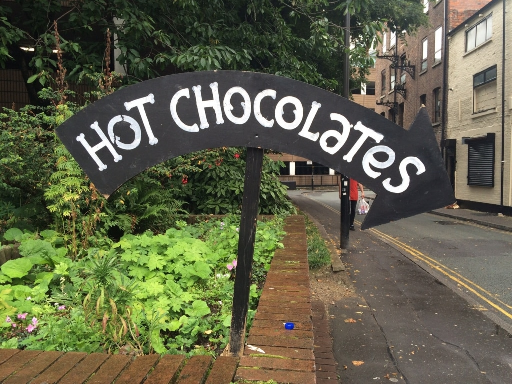 "A curved arrow sign saying ""hot chocolates"" stuck into a flower bed"