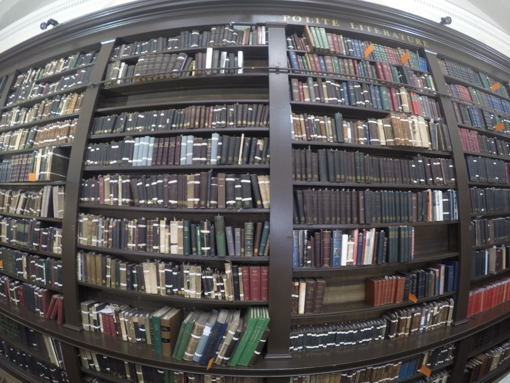 A fish eye shot of old library books on shelves